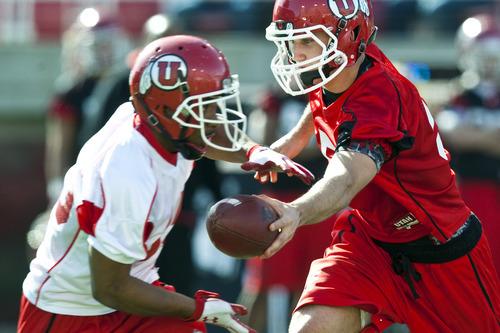 Chris Detrick  |  The Salt Lake Tribune Utah Utes quarterback Chase Hansen hands off to John White during practice at Rice-Eccles Stadium Tuesday March 20, 2012.