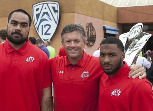 Utah football head coach Kyle Wittingham, center, is flanked by defensive tackle Star Lotulelei, left, running back John White at the Pac-12 Media Day in Los Angeles Tuesday, July 24, 2012. (AP Photo/Damian Dovarganes)