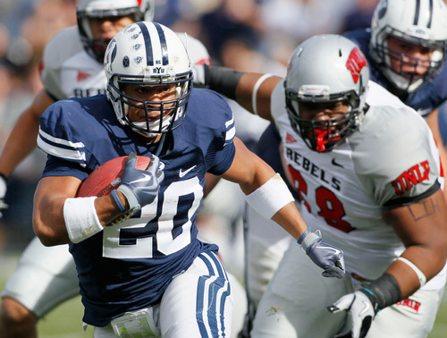 Colin E. Braley  |  AP file photo In this November 2010 photo, BYU tailback Joshua Quezada (20) rushes for a first down as UNLV defensive lineman Nate Halloway (68) chases during the first half of an NCAA college football game at LaVell Edwards Stadium in Provo.