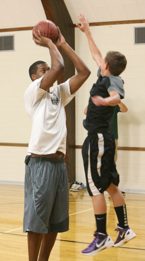 Steve Griffin | The Salt Lake Tribune   Beau Bateman, 13, jumps out of the gym as he tries to block the shot of Utah Jazz forward, Derrick Favors, during the Jazz player's visit to  Tabiona, Utah and their Junior Jazz program Monday July 30, 2012.