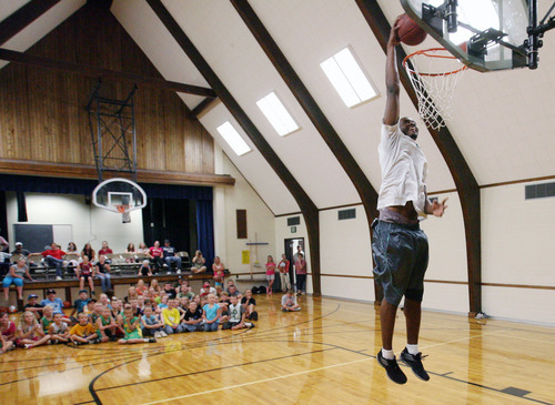 Steve Griffin | The Salt Lake Tribune   Utah Jazz forward, Derrick Favors, dunks the ball in the Tabiona LDS church gym, during the Jazz player's visit to Tabiona, Utah and their Junior Jazz program Monday July 30, 2012.