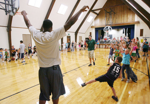 Steve Griffin | The Salt Lake Tribune   Utah Jazz forward, Derrick Favors, throws his arms in the air as he celebrates his team's victory in a passing game during his visit to  Tabiona, Utah and their Junior Jazz program Monday July 30, 2012.