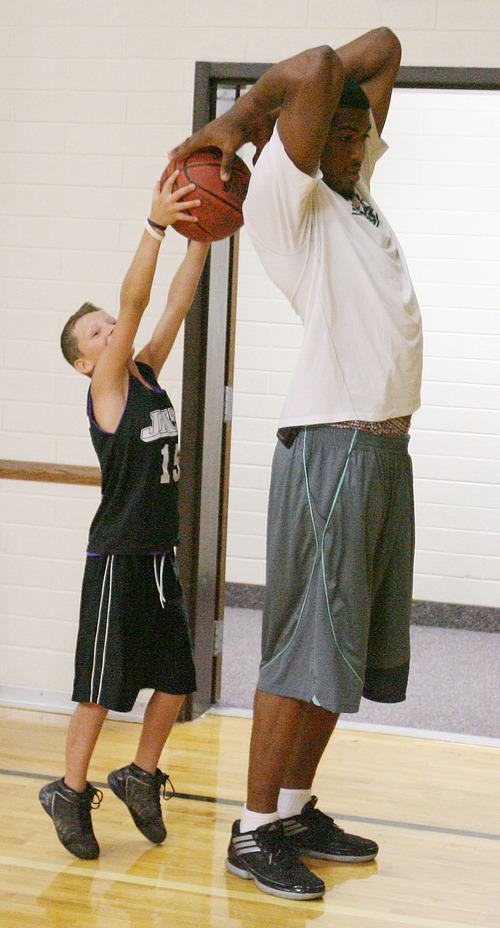 Steve Griffin | The Salt Lake Tribune   Kade Stewart, 9, reaches from his tip toes as he takes a pass from Utah Jazz forward, Derrick Favors, during the Jazz player's visit to  Tabiona, Utah and their Junior Jazz program Monday July 30, 2012.