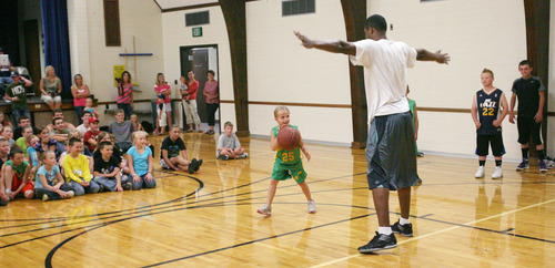 Steve Griffin | The Salt Lake Tribune   Mersadie Rhoades, 7, looks to drive around Utah Jazz forward, Derrick Favors, during the Jazz player's visit to  Tabiona, Utah and their Junior Jazz program Monday July 30, 2012.