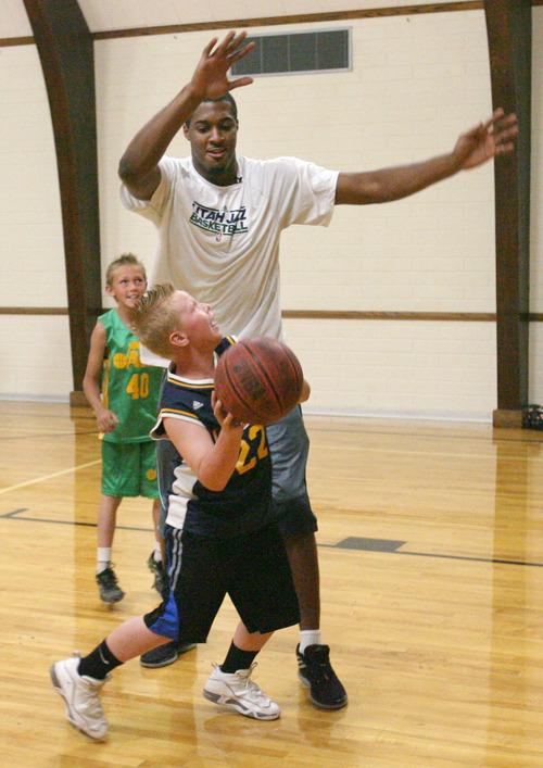 Steve Griffin | The Salt Lake Tribune   Hayes Giles, 11, posts up Utah Jazz forward, Derrick Favors, during the Jazz player's visit to Tabiona, Utah and their Junior Jazz program Monday July 30, 2012.