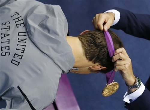 United States' Michael Phelps has his 18th gold medal placed around his neck at the Aquatics Centre in the Olympic Park during the 2012 Summer Olympics in London, Saturday, Aug. 4, 2012. (AP Photo/Julio Cortez)