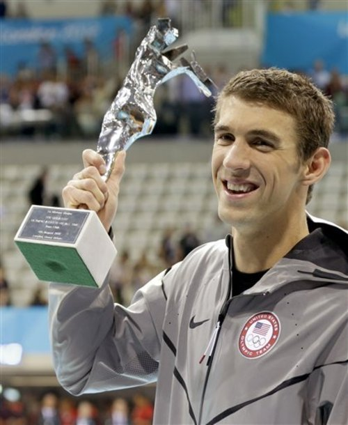 United States' swimmer Michael Phelps holds up a silver trophy after being honored as the most decorated Olympian at the Aquatics Centre in the Olympic Park during the 2012 Summer Olympics in London, Saturday, Aug. 4, 2012. Phelps was honored with a special individual ceremony after concluding his record-breaking career Saturday as the most decorated Olympian. Phelps pushed the United States in front to win the medley relay Saturday in the final swimming event of the London Games, after which he is retiring.(AP Photo/Lee Jin-man)