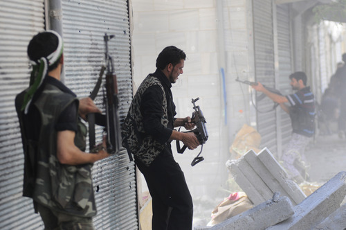 In this Wednesday, Aug. 1, 2012 photo, a Free Syrian Army soldier fires his weapon during clashes with Syrian government forces in Saladin neighborhood, in Aleppo, Syria. (AP Photo/Alberto Prieto)