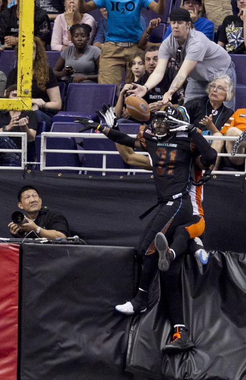 PNI0805-spt rattlers  073012419tk   --  8/4/12- An arena football fan reaches out to catch as pass as Arizona Rattlers defender Brandon Andersonblocks a pass intended for the Utah Blaze during the second quarter of Saturday's playoff game at U.S. Airways Center. Pat Shannahan/The Arizona Republic