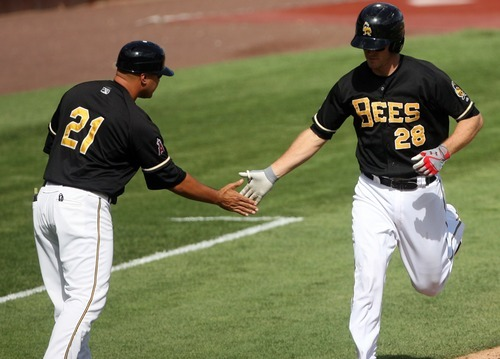Kim Raff | The Salt Lake Tribune Salt Lake Bees player (right) John Hester gets a hand from manager Keith Johnson after hitting a two run home run against the Oklahoma City Redhawks at Spring Mobile Ballpark in Salt Lake City, Utah on August 5, 2012.