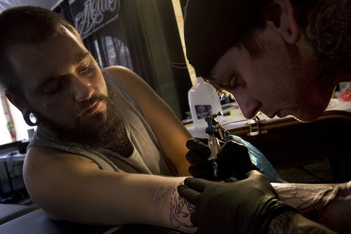 Scott Sommerdorf     The Salt Lake Tribune              Spencer Webb of Salt Lake, left, has work done by tattoo artist Justin Harris  at the first annual Park City Tattoo Convention at the Yarrow Hotel, Sunday, August 5, 2012