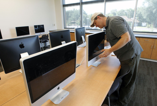 Al Hartmann  |  The Salt Lake Tribune   Lars Andersen teacher and technical coordinator sets up computers in a digital classroom at Innovations High School at 1700 South and State Street which will open this Fall.  The new building will connect to the Salt Lake Community College campus next door.