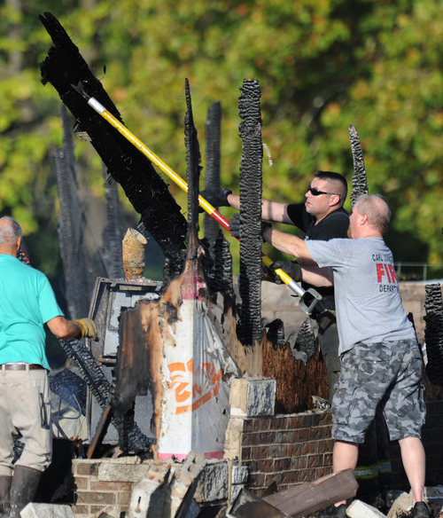 Firefighters maneuver debris following a fire at the Islamic Society of Joplin, Mo., Monday, Aug. 6, 2012, in Joplin, Mo. The fire was the second fire to hit the Islamic center in little more than a month. (AP Photo/The Joplin Globe, T. Rob Brown) MANDATORY CREDIT