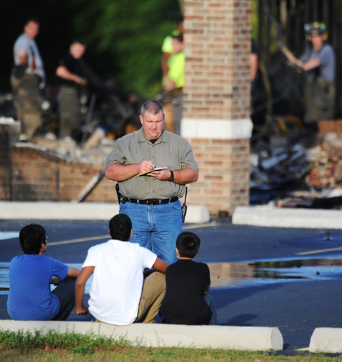An investigator asks questions of witnesses as firefighters work in the background, at the Islamic Society of Joplin mosque, Monday, Aug. 6, 2012, in Joplin, Mo. The fire was the second fire to hit the Islamic center in little more than a month. The boys, pictured from left, are: Haaris Rehman, 12; Omar Ahmed, 15; and Humza Rehman, 10. (AP Photo/The Joplin Globe, T. Rob Brown) MANDATORY CREDIT