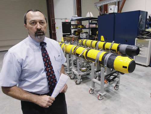Christopher Egan, an unmanned systems customer advocate, stands near a pair of unmanned underwater vehicles (UUV) in a lab at the Naval Undersea War Center in Middletown, RI., Tuesday, July 31, 2012.  Narragansett Bay is the testing ground for the Naval Undersea Warfare Center where the Navy is working toward its goal of achieving a squadron of self-driven, undersea vehicles. (AP Photo/Stephan Savoia)