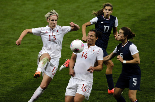 Canada's Sophie Schmidt, left, kicks the ball past Canada's Melissa Tancredi, center, as United States' Tobin Heath runs behind next to the United States' Kelley O'Hara, right, during the semi-final women's soccer match between the USA and Canada in the 2012 Summer Olympics, Monday, Aug. 6, 2012, at Old Trafford in Manchester, England. (AP Photo/Ben Curtis)