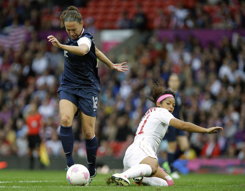 United States' Lauren Cheney, left, battles for the ball against Canada's Desiree Scott, right, during their semifinal women's soccer match between the USA and Canada at the 2012 London Summer Olympics, in Manchester, England, Monday, Aug. 6, 2012. (AP Photo/Hussein Malla)