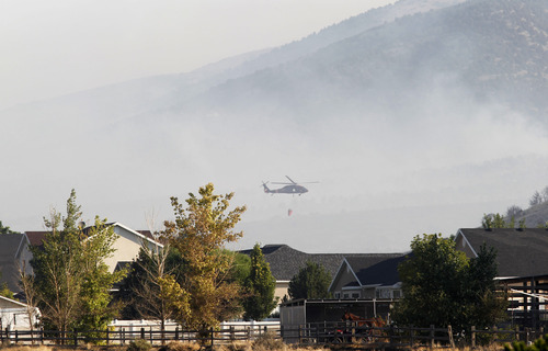 Al Hartmann  |  The Salt Lake Tribune   Helicopters make water drops on the Pinyon Fire on Camp Williams land north of Eagle Mountain on Tuesday, Aug. 7.