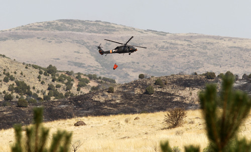 Al Hartmann  |  The Salt Lake Tribune   Helicopters continued to drop water on the 2,960 acre Pinyon Fire burning north of Eagle Mountain on Camp Williams land with 0 percent containment as of noon on Tuesday, Aug. 8.
