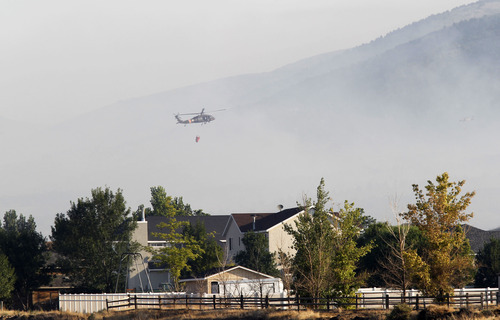 Al Hartmann  |  The Salt Lake Tribune   Helicopters make water drops on the Pinyon Fire on Camp Williams land north of Eagle Mountain Tuesday, Aug. 7.