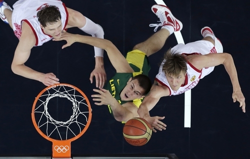 Russia's Andrei Kirilenko, right, and Timofey Mozgov, left, battle Lithuania's Paulius Jankunas, center, for a rebound during a men's quarterfinals basketball game at the 2012 Summer Olympics, Wednesday, Aug. 8, 2012, in London. (AP Photo/Charles Krupa)