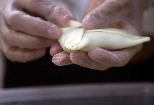 Kim Raff | The Salt Lake Tribune Nichelle Jesen wraps empanadas in the kitchen of Martin's Fine Desserts in Salt Lake City on August 3, 2012.