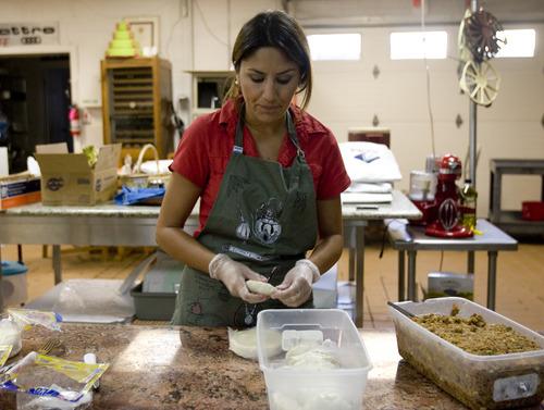Kim Raff | The Salt Lake Tribune Ana Valdemoros wraps beef empanadas in the kitchen of Martin's Fine Desserts in Salt Lake Cityon August 3, 2012.