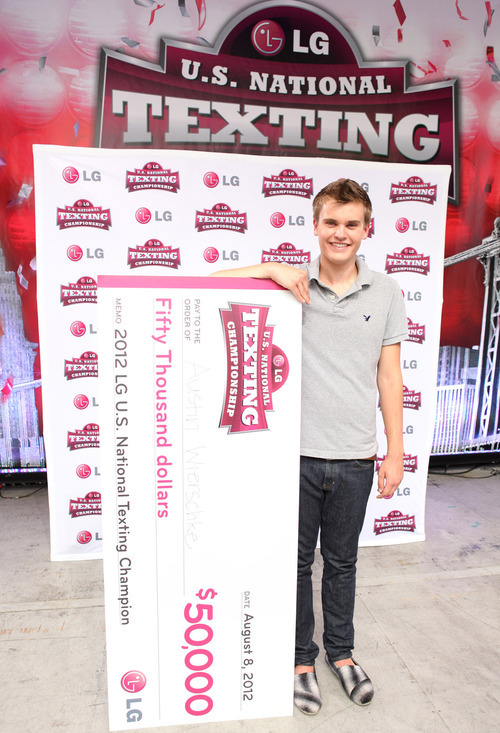 In this photo provided by LG, Austin Wiershcke, of Rhinelander, Wis., poses with his ceremonial $50,000 check after winning the LG U.S. National Texting Championship for the second year in a row Wednesday, Aug. 8, 2012 in New York's Times Square. (AP Photo/LG)