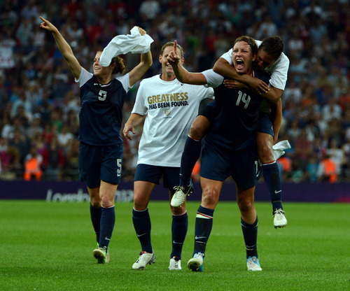 USA's Abby Wambach (14) and Shannon Boxx (7), far right, celebrates their 2-1 win against Japan for the Women's Football Gold Medal Match at Wembley Stadium for the London 2012 Olympics in London, England on Thursday, Aug. 9, 2012.  (Nhat V. Meyer/Mercury News)