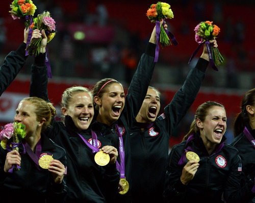USA's Alex Morgan (13), center-left, celebrates their 2-1 win against Japan for the Women's Football Gold Medal Match at Wembley Stadium for the London 2012 Olympics in London, England on Thursday, Aug. 9, 2012.  (Nhat V. Meyer/Mercury News)