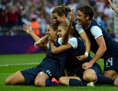 USA's Carli Lloyd (10) celebrates her first goal with Kelley O'Hara (5), Alex Morgan (13), and Abby Wambach (14) in the first half of their game against Japan for the Women's Football Gold Medal Match at Wembley Stadium for the London 2012 Olympics in London, England on Thursday, Aug. 9, 2012.  (Nhat V. Meyer/Mercury News)