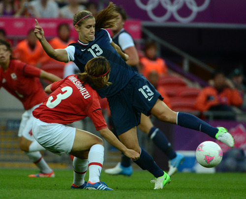 USA's Alex Morgan (13) fights for the ball against Japan's Azusa Iwashimizu (3) in the first half of their game for the Women's Football Gold Medal Match at Wembley Stadium for the London 2012 Olympics in London, England on Thursday, Aug. 9, 2012.  (Nhat V. Meyer/Mercury News)