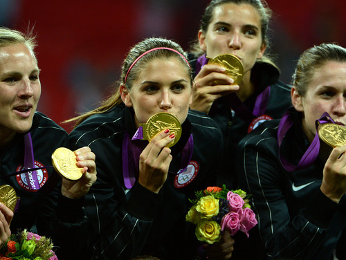 USA's Alex Morgan (13), center left, kisses the gold medal as they celebrate their 2-1 win against Japan for the Women's Football Gold Medal Match at Wembley Stadium for the London 2012 Olympics in London, England on Thursday, Aug. 9, 2012.  (Nhat V. Meyer/Mercury News)