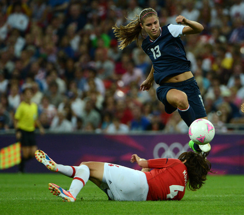USA's Alex Morgan (13) jumps over Japan's Saki Kumagai (4) in the second half of their game for the Women's Football Gold Medal Match at Wembley Stadium for the London 2012 Olympics in London, England on Thursday, Aug. 9, 2012.  (Nhat V. Meyer/Mercury News)