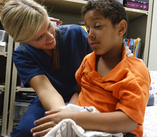 Leah Hogsten  |  The Salt Lake Tribune Registered nurse Ashley Kirkland wakes up Iraqi immigrant Hussien Alsaedi, 6, who is groggy from receiving 10 fillings, 1 crown and an extraction. Donated Dental Services of Salt Lake City provides sedation one day a month for kids where they can get multiple dental needs met all at once.
