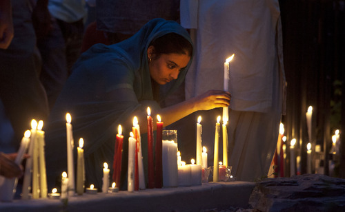 Steve Griffin | The Salt Lake Tribune   Manjot Kuar places a candle outside the Sikh Temple of Utah, during a candlelight vigil for the victims of the shooting at the Wisconsin Sikh Temple. The service was at the temple in Taylorsville, Utah Wednesday August 8, 2012.