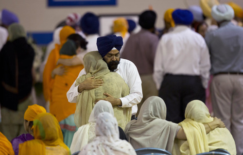 Mourners provide comfort at the funeral and memorial service for the six victims of the Sikh temple of Wisconsin mass shooting in Oak Creek, Wis., Friday, Aug 10, 2012. The public service was held in the Oak Creek High School. Three other people were wounded in the shooting last Sunday at the temple.   Wade Michael Page, 40, killed five men and one woman, and injured two other men. Authorities say Page then ambushed the first police officer who responded, shooting him nine times and leaving him in critical condition. A second officer then shot Page in the stomach, and Page took his own life with a shot to the head. (AP Photo/Jeffrey Phelps)