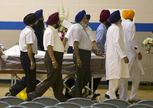 Sikh temple members bring in a casket for the funeral and memorial service for the six victims of the Sikh Temple of Wisconsin mass shooting in Oak Creek, Wis., Friday, Aug 10, 2012. The public service was held in the Oak Creek High School. Three other people were wounded in the shooting last Sunday at the temple. (AP Photo/Jeffrey Phelps)