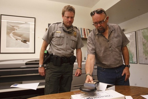 Leah Hogsten  |  The Salt Lake Tribune Scott Brown, chief ranger (left) and Dave Worthington, chief resources management and science (right) at Capitol Reef National Park, operate a tagging device that injects transponders into the endangered cactus as part of federal efforts to protect the endangered fauna.