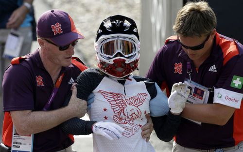 United States' Alise Post is helped out of the track after crashing during a BMX cycling women's semifinal run at the 2012 Summer Olympics in London, Friday, Aug. 10, 2012. (AP Photo/Matt Rourke)