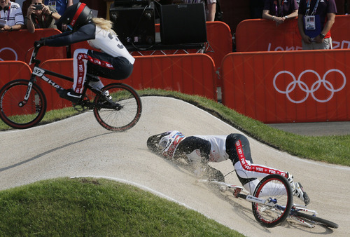 United States' Brooke Crain (32) passes  Alise Post who crashed in a BMX cycling women's semifinal run during the 2012 Summer Olympics in London, Friday, Aug. 10, 2012. (AP Photo/Christophe Ena)