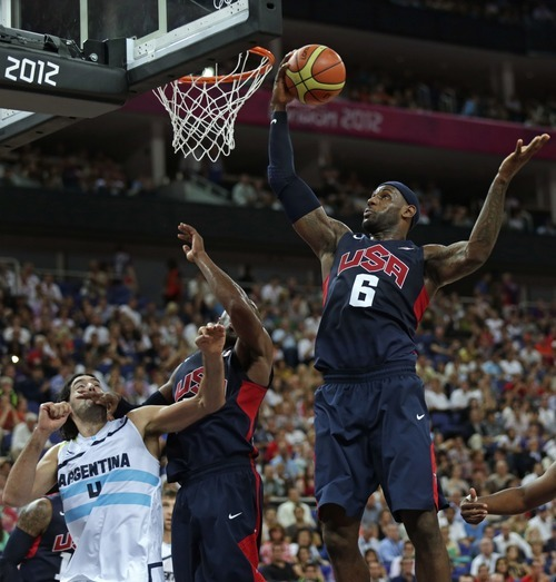 United States' LeBron James, right, grabs a rebound as teammate Kobe Bryant blocks out Argentina's Luis Scola during a men's semifinals basketball game at the 2012 Summer Olympics, Friday, Aug. 10, 2012, in London. (AP Photo/Charles Krupa)