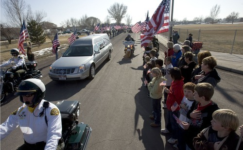 Steve Griffin  |  The Salt Lake Tribune  Delta -  Hundreds of people holding flags line 350 east in Delta as the body of, Josie Greathouse Fox, the Millard County deputy gunned down during a traffic stop near Delta, is driven to the cemetery after services in Delta Monday Jan 11, 2010.