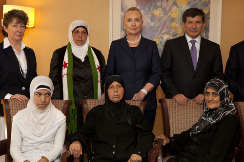 Turkey's Foreign Minister Ahmet Davutoglu, top right, and U.S. Secretary of State Hillary Rodham Clinton pose for a photograph with Syrian refugees after meeting with the group in Istanbul, on Saturday, Aug. 11, 2012. (AP Photo/Jacquelyn Martin, Pool)