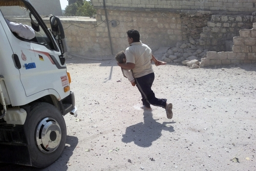 This citizen journalism image released by the Shaam News Network and accessed Saturday Aug. 11, 2012, purports to show a man saving a wounded child in Jisr ash-Shugur, in the Idlib Governorate, in northwestern Syria, Friday, Aug. 10, 2012. (AP Photo/Shaam News Network, SSN) THE ASSOCIATED PRESS IS UNABLE TO INDEPENDENTLY VERIFY THE AUTHENTICITY, CONTENT, LOCATION OR DATE OF THIS HANDOUT PHOTO