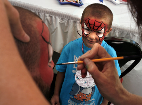 Scott Sommerdorf  |  The Salt Lake Tribune              Alexander Aparicio watches as his father Rigo also gets a Spiderman facepaint from Susan Ostler at the Back to School