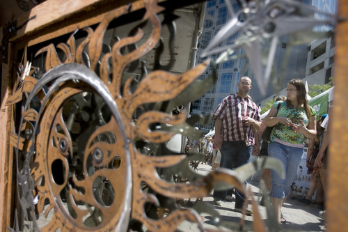 Kim Raff   The Salt Lake Tribune People walking by are reflected in a mirror at the Raw Materials Sculpture and Design booth during the 4th annual Craft Lake City Utah's DIY Festival at the Gallivan Center in Salt Lake City, Utah on August 11, 2012.
