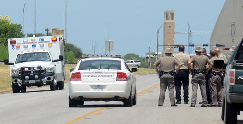 Texas State troopers and Brazos Valley lawmen watch as an ambulance believed to be carrying one of their downed fellow officers speeds off to a hospital in College Station, Texas, Monday, Aug. 13, 2012. Police say at least one law enforcement officer and one civilian have been killed in a shooting near Texas A&M University's campus. Assistant Chief Scott McCollum says the gunman also was shot Monday before being taken into custody.  (AP Photo/Bryan-College Station Eagle, Dave McDermand)