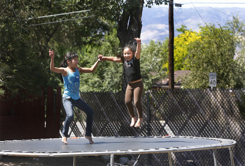 Scott Sommerdorf  |  The Salt Lake Tribune              Mauro Soriano's daughters play on their backyard trampoline. The family now shares their home with Soriano's brother Julian and his parents. As a result of the economic downturn and mortgage crisis, the families may end up having to move into an apartment.