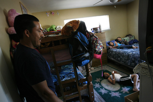 Scott Sommerdorf  |  The Salt Lake Tribune              Mauro Soriano checks on his three children -- who live in one bedroom in the home now sheltering his family, his brother and his parents.